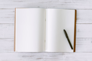 Open book with blank pages on wooden background