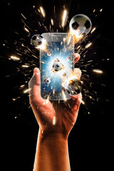 Burning soccer balls flies from the smartphone, black isolated