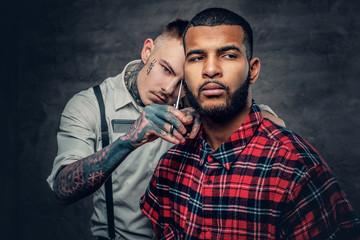 Tattooed barber cuts the beard to a Black bearded male.