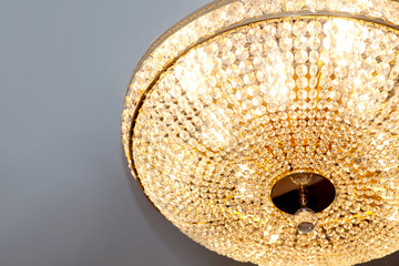 Round beautiful golden chandelier on the ceiling