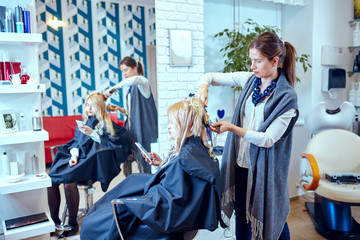 Hair styling in a beauty salon .