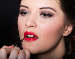 Apply lipstick with a red brush
