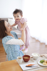 Mother Lifting Baby Girl at Breakfast Table