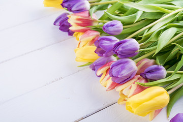 Colorful tulips on a white wooden table..