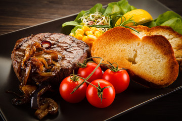 Grilled steak with toasted buns on wooden background