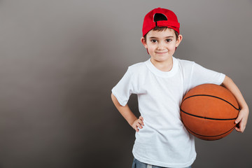 Smiling little boy in cap with orange basketball ball