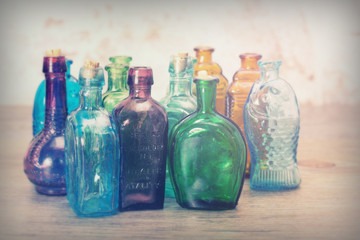 Coloured glass bottles on a rustic background