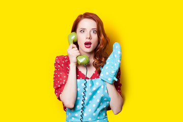 beautiful surprised young woman with retro phone and potholder on the wonderful yellow background