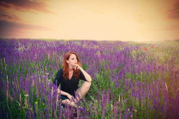 beautiful young woman sitting and relaxing on the wonderful blooming lavender field