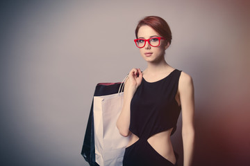 beautiful young woman with shopping bags on the wonderful grey background