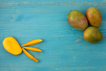 Three fresh mango and slices on a blue wooden background.