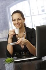 Happy businesswoman having coffee break