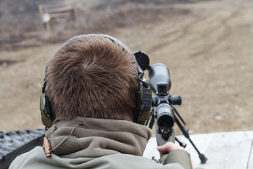 A man shoots a rifle. Rifle shooting with optical sight outdoors by man.