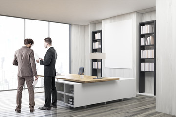 Two colleagues in a CEO office with gray walls