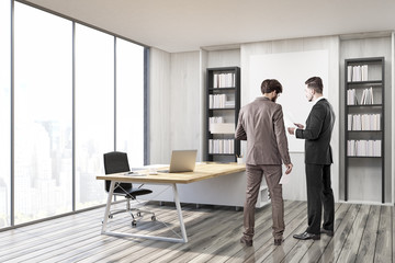 Two men in suits in CEO office with gray walls