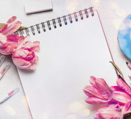 Womens springtime workspace with pale pink  tulips, notebook or sketchbook and colorful brush markers ,  top view