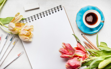 Womens springtime workspace with  pretty tulips, notebook or sketchbook , colorful brush markers and coffee cup, top view