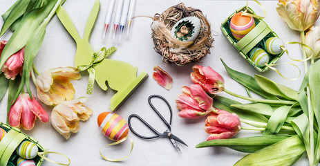 Easter workspace with pretty tulips, shears and various deco eggs in basket, top view