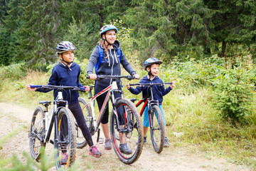 Young girl with her mother and small brother enjoying cycling in forest. Family riding bike concept background