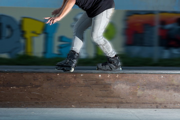 Young man rollerblading. Rollerblader near graffiti. Not afraid of speed. Legs of person on inline skates close up. driving concept on rollers on a stage.