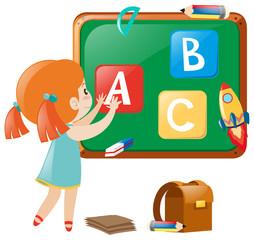 Little girl posting english alphabets on board