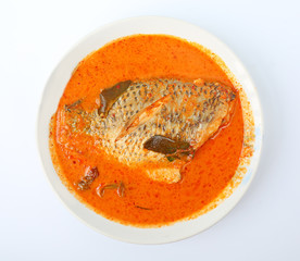 Spicy hot tilapia fish curry in white plate against white background