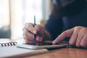 A woman's hands writing on notebook and using smartphone on wooden table in modern cafe