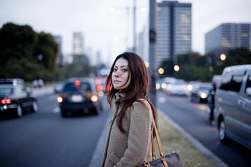 Woman waiting to cross the street, Tokyo Prefecture, Honshu, Japan