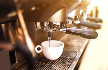 coffee machine. coffee machine preparing fresh coffee and pouring into red cups at restaurant, bar or pub.
