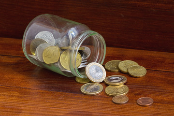 Glass jar with euro coins scattered. Finansial concept.