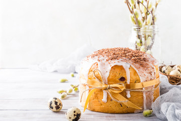 Easter orthodox sweet bread, kulich and colorful quail eggs on light background. Easter holidays breakfast concept with copy space.
