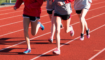 Four girls training together on a red track in spikes