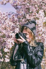 Preciosa chica joven, hipster, haciendo fotos con su cámara en primaver
