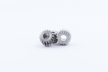 Isolated metal pinions gear. The iron gear on a white background. Pinions in the gearbox. Parts to the gear mechanism. Sprockets to clockwork. Shiny gear ready for assembly.
