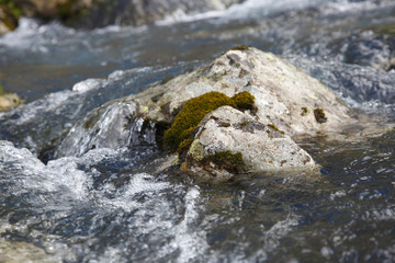 Granite stone in a stormy creek, natural background.