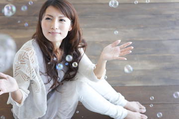 Young woman sitting on floor, soap bubbles over woman
