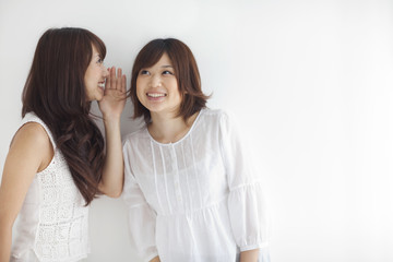 Young woman whispering friend's ear, white background, copy space