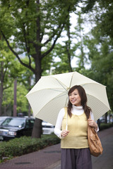 Young woman with umbrella, smiling