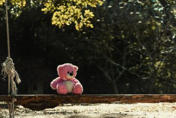 Pink teddy bear on a swing in the garden.