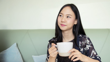 Asia woman holding cup of coffee and smiling