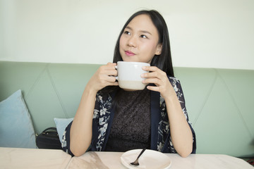Portrait of a cheerful asia woman suggesting to drink coffee