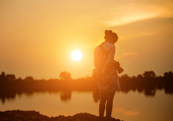 Woman holding a camera in  sunset