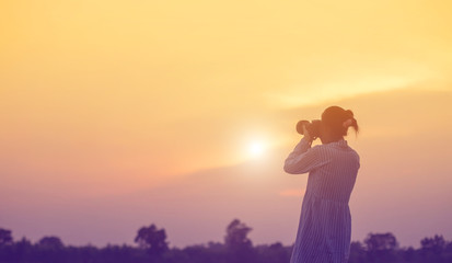 Woman holding a camera in  sunsets