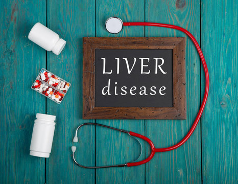 """Blackboard with text """"Liver disease"""", pills and stethoscope on wooden background"""