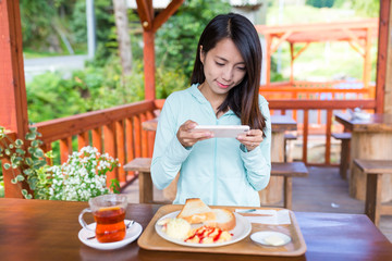 Woman taking photo on her breakfast before eating