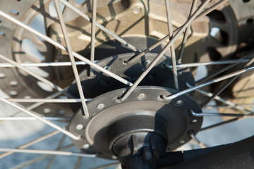 attachment of the spokes to the hub of the front wheel of the motorcycle closeup