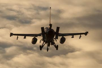 Avión de guerra F-16 aterrizando al anochecer