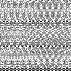 Seamless lacy texture. Black lace small flowers on a white background.
