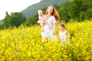 Wall Murals Happy family of mother and children run in the meadow of yellow flowers