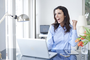 Success guaranteed. Shot of an overjoyed young businesswoman sitting at desk in front of laptop and celebrating the success.